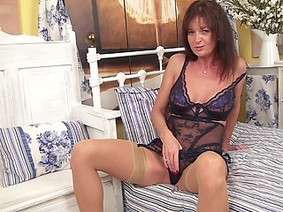 Brunette mature Lucy Heart plays with her piercer clit on the bed