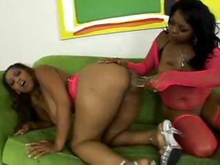 Two black sluts in pink lingerie oil their asses and fuck their pussies with toy