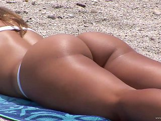 Hot babe shows off her firm tush and big tits on the beach