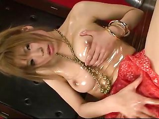 Ai Sakura oils up her big tits and juicy pussy to make
