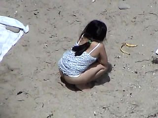 I recorded a horny brunette pissing in the sand at the beach