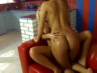 Two sexy, oiled up lesbians play on the couch