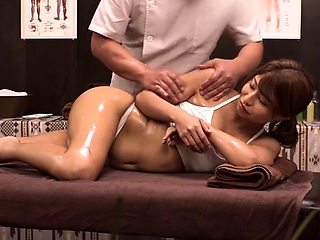 Stunning Oriental babe sexually satisfied on the massage bed