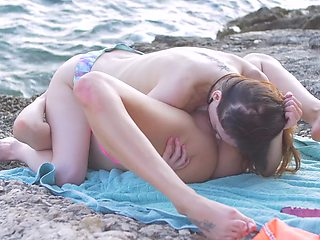 Two girls are at the beach, sharing a dildo with one another