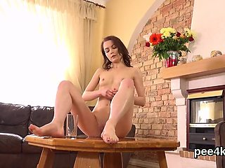 Stunning cutie is pissing and finger fucking shaven snatch