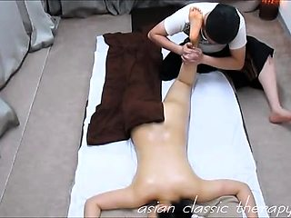 Slim Asian babe lies on her belly and enjoys a nice massage