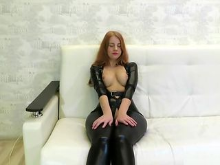 Redhead girl in tight suit and high heels shows her ass