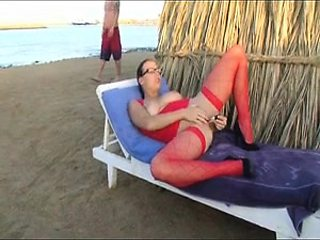 Buxom babe in sexy red lingerie masturbates on the beach