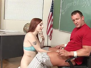 A redhead is on top of her horny teacher in the classroom