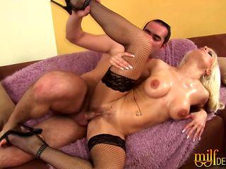 Cougar with huge false boobs giving a tit job