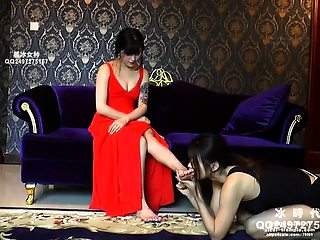 Slender Oriental babe has her lesbian slave licking her feet