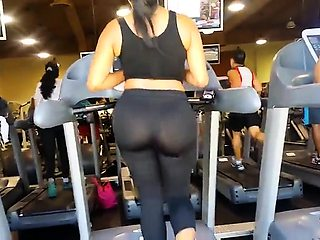 Voyeur finds a sexy brunette with a fabulous ass in the gym