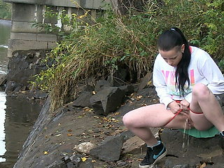 Raven Haired Girl Pees Near The River